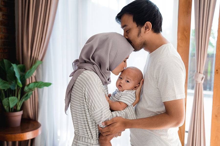 Individual Life Insurance - Father and Mother Standing at Home Holding Their Baby
