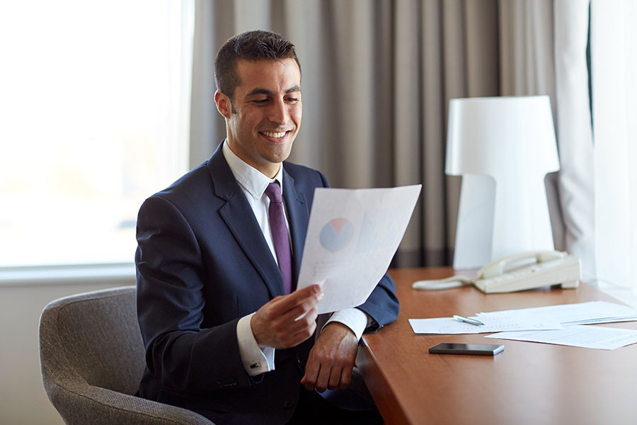 Policy Review - Business Man Sitting in Office Reviewing Paperwork